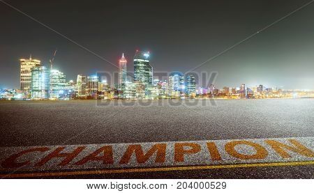 View of the empty asphalt road with champion word and city skyline background . Night scene .