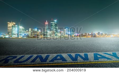 View of the empty asphalt road with runawy word and city skyline background . Night scene .