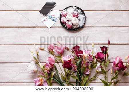 Sweet and blossomed background on wooden backdrop. Colorful zephyrs on plate and white, pink and deep purple eustoma, smartphone and post cards with free space nearby
