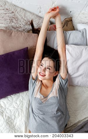 Young woman stretching arms under sunbeams top view. Past dreams in the morning, calmness and relaxation, staying in bed for a while concept
