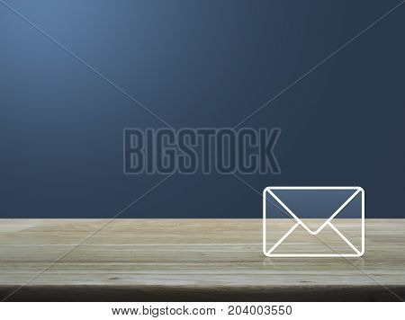 Mail icon on wooden table over light gradient blue background Contact us concept