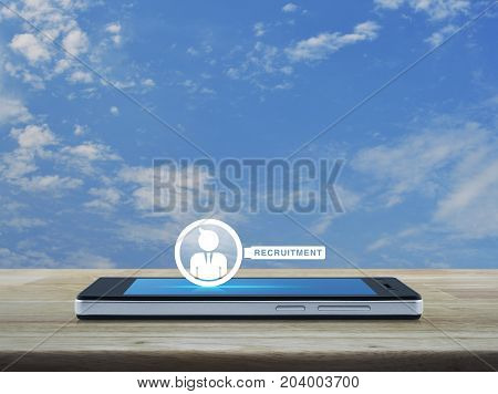 Businessman with magnifying glass icon on modern smart phone screen on wooden table over blue sky with white clouds Recruitment concept