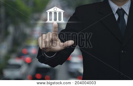 Businessman pressing bank icon over blur of rush hour with cars and road Business banking concept