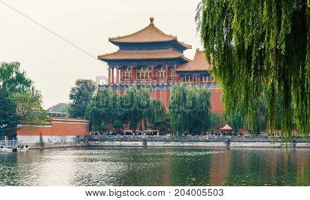 Beijing, China - Oct 30, 2016: Quezuo Gate across the Tongzi River moat. Outside the Forbidden City (Gu Gong, Palace Museum), along Donghuamen Road. Hazy day.