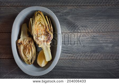 Artichokes and lemons on the plate. This product has one of the highest antioxidant capacities. Traditional vegetables in italian cuisine. Gray wooden background