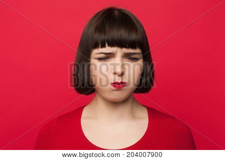 Unpleasant smell. Bad atmosphere for girl. Young woman blowing out cheeks, upset beautiful female