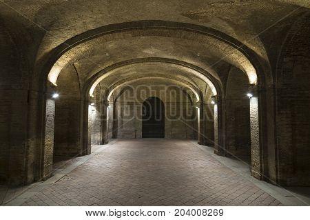 Ancient palace of Pilotta ( Palazzo della Pilotta ) Parma at night Europe. Ground floor stone arches illuminated lanterns . Old brick masonry . Tourist attraction