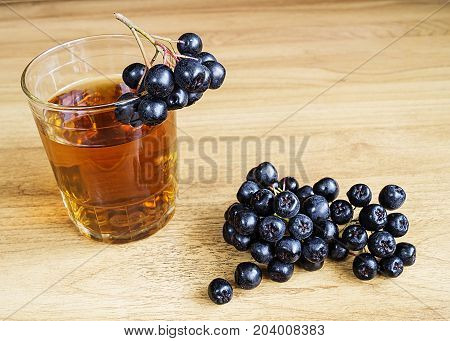 Juice of rowanberry in cup on wooden table with branch of rowanberry