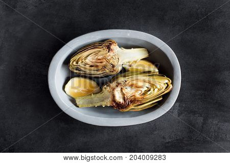 Artichokes and lemons on the plate. This product has one of the highest antioxidant capacities. Traditional vegetables in italian cuisine. Top view