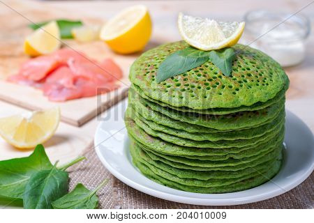 A stack of pancakes of spinach. On the table along with the fish, spinach and lemon wedges. Shallow DOF