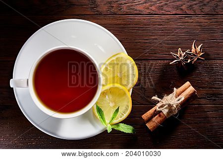 White porcelain cup of tea with white and brown sugar cubes, cinnamon sticks, honey, lemon, mint leaves and tea strainer on wooden rustic table. Top view.