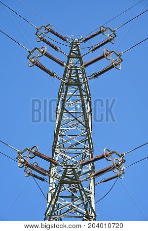 High electricity pylon against blue sky in summer