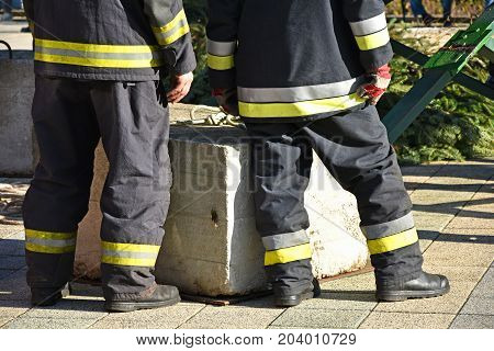 Firefighters are waiting outdoor next to a concrete block