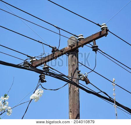 Electricity pylon with wires against blue sky