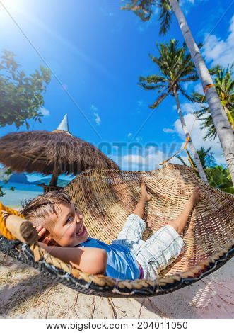 Cheerful little boy relaxing on a tropical beach in hammock.
