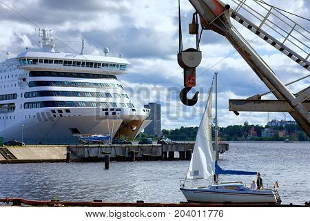 Loading a passenger ferry in the port of Riga against the backdrop of a sailing yacht on a summer day