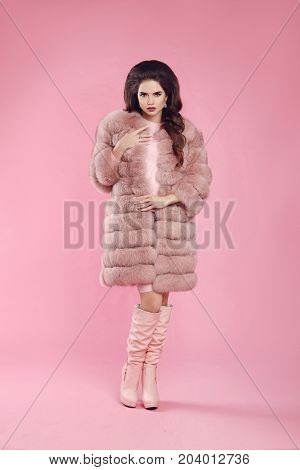Fashionable woman in fur coat and leather high boots, lady portrait over pink studio background. Beautiful brunette model in fashion winter style.