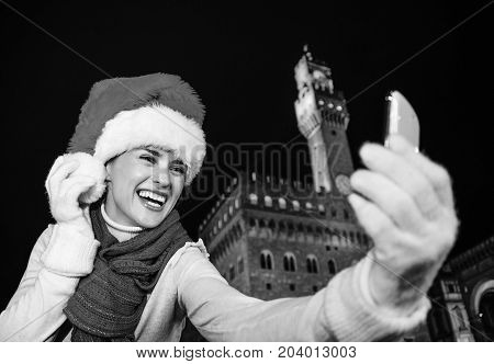 Woman In Christmas Hat In Front Of Palazzo Vecchio Taking Selfie