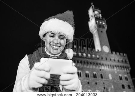 Woman In Christmas Hat In Florence Viewing Photos On Camera