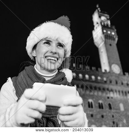 Smiling Woman In Christmas Hat In Florence, Italy Writing Sms