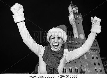 Trip full of inspiration at Christmas time in Florence. Portrait of happy young woman in Christmas hat in the front of Palazzo Vecchio in Florence Italy rejoicing poster