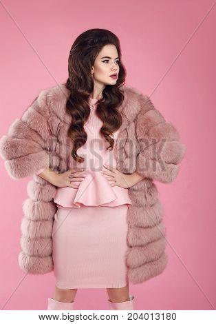 Beauty fashion elegant woman in fur coat over pink. Fashionable brunette lady wearing stylish dress posing isolated on studio background. Glamour luxury vogue style apparel.