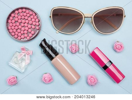 Modern urban woman essentials: foundation, blusher, lipstick, perfume, sunglasses. Contents of cosmetic bag