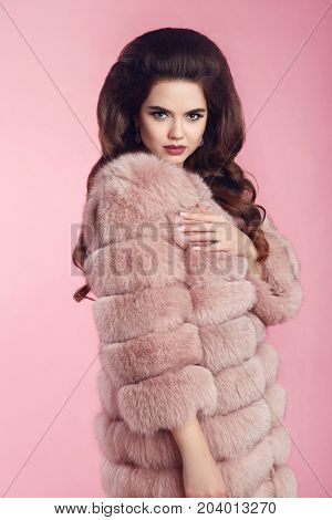 Fashion photo of woman in fur coat over pink studio background. Winter lady portrait. Luxury glamour girl with elegant hairstyle.