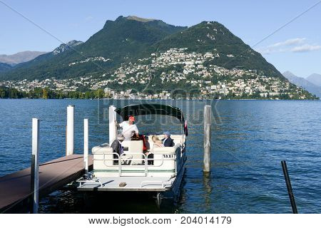 Lugano Switzerland - 6 September 2015: A taxi boat embarks its customers to bring them on a tour of Lake Lugano