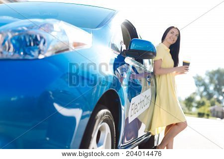 Delicious drink. Attractive pleasant young woman holding a coffee cup and leaning on the car while enjoying her day