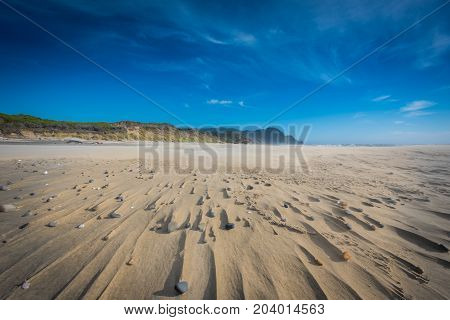 Wispy Clouds Above Stones And Sandy Streaks