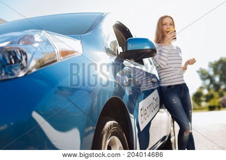 Modern electro car. Selective focus of a modern blue electro car being parked on the street with a nice attractive woman standing near it