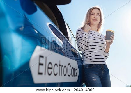 My automobile. Pleasant good looking blonde woman holding a cup of coffee and drinking it while standing near her car
