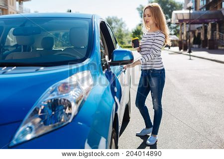 Female driver. Confident nice young woman standing on the street and holding a cup of coffee while opening her car