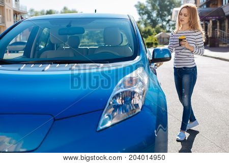 Near the car. Attractive pleasant blonde woman standing on the street and holding the handle of a car door while opening it