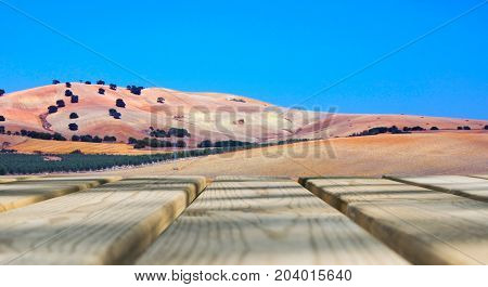 Wooden board empty table in front of blue sky & mountain background. Perspective wood floor over field and mountain & summer concepts.