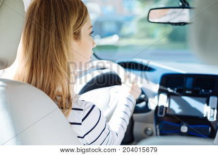 Careful driver. Nice pleasant young woman looking at the road and driving carefully while sitting behind the wheel