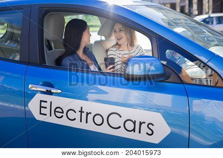 Womens gossips. Happy positive joyful friends sitting in the car and talking to each other while telling different gossips