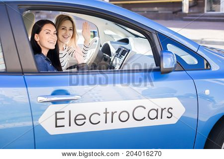 Pleasant meeting. Delighted happy young women sitting in the car and waving their hands while seeing a friend