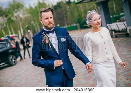 Happy newlywed couple on a walk in old European town street, gorgeous bride in white wedding dress together with handsome groom in stylish suit and beard.