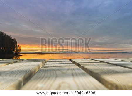 Wooden board empty table in front of sunset sea & sky background. Perspective wood floor over sea and sunset sky & summer concepts.