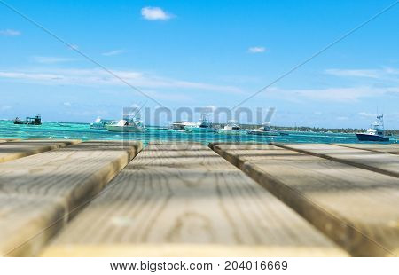 Wooden board empty table in front of blue sea yachts & sky background. Perspective wood floor over sea yachts and sky beach & summer concepts.