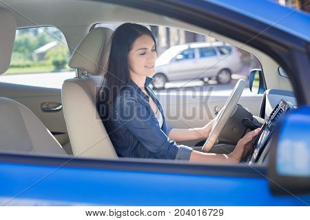 Time to go. Attractive nice pretty woman holding the wheel and starting the car while being ready to leave
