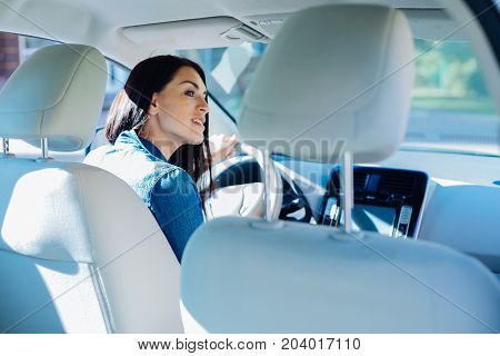 Behind the wheel. Attractive pleasant young woman sitting in the car and driving it while being a skillful driver