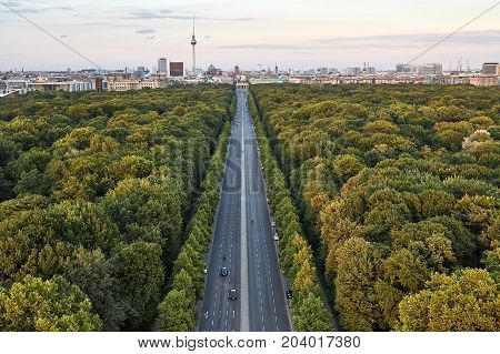 Panoramic view at the highway between green trees and the cityscape of Berlin with Television Tower and Brandenburg Gate. Sun shines onto trees tops. Horizontal.