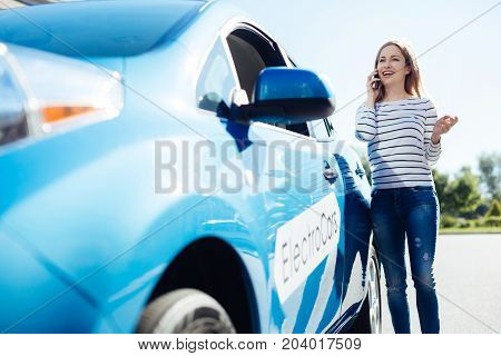 Distance communication. Delighted positive nice woman standing near her car and smiling while talking on the phone
