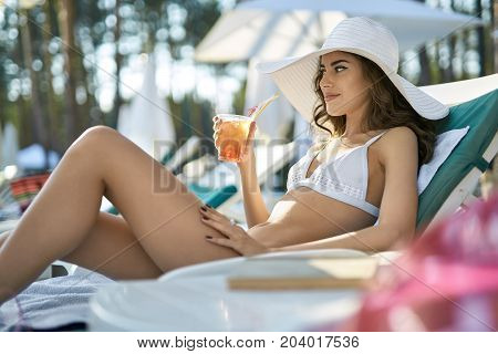 Joyful girl in a white swimsuit and hat lies on the sun lounge outdoors. She holds a cocktail in the right hand and looks forward with a smile. Horizontal.