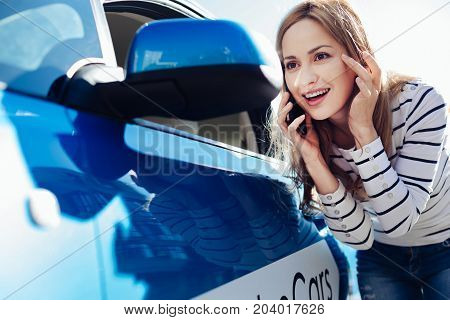Always beautiful. Joyful attractive pretty woman leaning forward and looking into the side view mirror while having a phone conversation