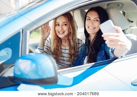 Great photo. Attractive positive beautiful women sitting in the car and smiling while taking a selfie