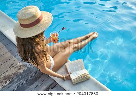 Amazing girl in a white swimsuit and a straw hat sits on the pool's edge outdoors. She touches the water with her legs and holds a cocktail and a book. Sun shines onto her body. Horizontal.